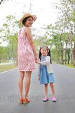 Mom and daughter holding hands in the outdoor nature garden stock photo