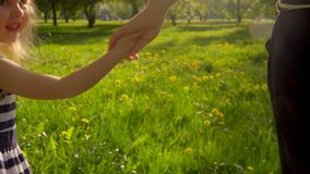 Mom and daughter holding hands. And walking in the garden stock video footage