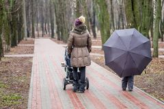 Mom and daughter   walking together with stroller Royalty Free Stock Photo