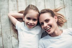 Mom with daughter at home. Attractive young women and her little charming daughter are having fun at home together. Sincere smiles and tenderness Royalty Free Stock Images