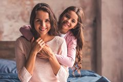 Mom and daughter at home. Beautiful mom and daughter are hugging, looking at camera and smiling while sitting on bed at home Stock Photo