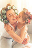Mom and daughter at home. Beautiful young mother and her daughter with hair curlers are sitting on bed at home. Cute little girl is kissing her mom Stock Images