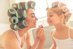Mom and daughter at home. Beautiful young mother and her daughter with hair curlers are sitting on bed at home. Mom is doing her daughter makeup Royalty Free Stock Photo