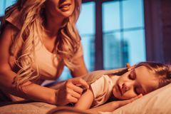 Mom and daughter at home. Good night, princess! Attractive young women with little cute girl are spending time together at home. Mom is putting daughter to bed Stock Photo