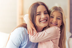 Mom and daughter at home. Portrait of beautiful young mother and her daughter hugging, looking at camera and smiling Royalty Free Stock Image