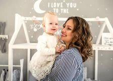 Mom and daughter are at home in the room, Mother`s Day. Mother holds daughter in her arms Royalty Free Stock Images
