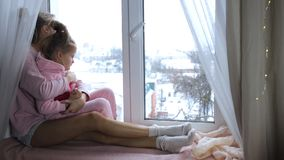 Mom and daughter hug. Sitting on the windowsill and look out the window stock video footage