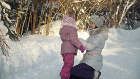 Mom and daughter hug in the suburbs in winter. stock video footage