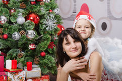 Mom and daughter hugging at the Christmas tree Royalty Free Stock Photography