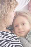 Mom and daughter hugging. Mom and little daughter laying on a bed and hugging stock photo