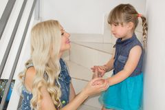 Mom and daughter in identical dresses are sitting on the stairs, blondes. stock images