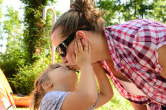 Mom and daughter kissing. Daughter kissing mom on camping trip Royalty Free Stock Images