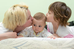 Mom and daughter kissing baby Royalty Free Stock Image