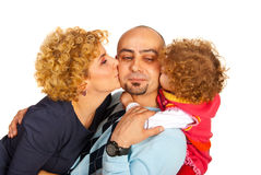 Mom and daughter kissing dad Stock Photo