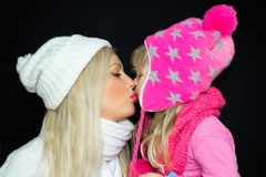 Mom and daughter are kissing in knitted hats on a black background. Happy family, smiles and joy. Studio photography stock image