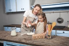 Mom and daughter in the kitchen cook Mafins. daughter breaks the egg over the flour.  stock photo