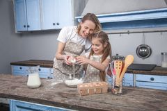 Mom and daughter in the kitchen cook Mafins. daughter breaks the egg over the flour.  stock photos