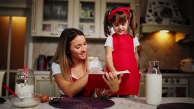 Mom and daughter in the kitchen in a red apron read the recipe cake in a notebook. Mom and daughter in the kitchen in a red apron read the recipe cake in a stock video footage