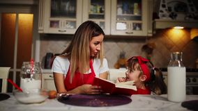 Mom and daughter in the kitchen in a red apron read the recipe cake in a notebook. Mom and daughter in the kitchen in a red apron read the recipe cake in a stock footage