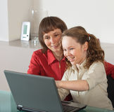Mom and daughter with laptop. Mother and teenager girl with laptop computer together at home royalty free stock photography