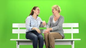 Mom and daughter laugh. Green screen. Mom and daughter laugh and sit on a white wooden bench. Green screen stock footage