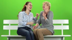 Mom and daughter laugh. Green screen. Slow motion. Mom and daughter are sitting on a bench and smile on talking on various topics. Green screen. Slow motion stock video
