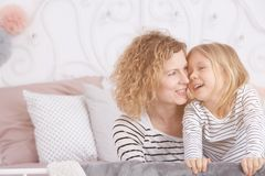 Mom and daughter laughing. Happy mom and daughter sitting on the bed and laughing royalty free stock photography
