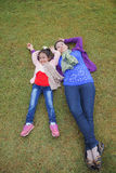 Mom and daughter are laying on the grass yard. Mother and daughter is happily smilling together laying on the grass yard royalty free stock photography