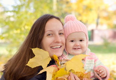 Mom and daughter with leaves. In autumn park stock images