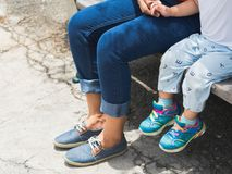 Mom and daughter legs sitting on the chair in the park. Happy Fa stock photo