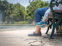 Mom and daughter legs sitting on the chair in the park. Happy Fa stock image