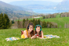Mom and daughter listening music in nature Stock Images
