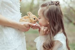 Mom, daughter and little rabbit. stock photos