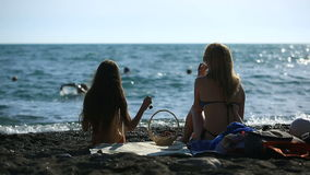 Mom and daughter with long hair in bathing suits, eating fruits and berries on a sea beach on a background of waves stock footage
