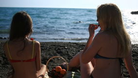 Mom and daughter with long hair in bathing suits, eating fruits and berries on a sea beach on a background of waves stock video