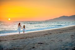 Mom and daughter in long white dresses walking to the beach. On a beautiful sunset royalty free stock photos