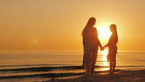 Mom and daughter are looking forward to a beautiful sunset over the sea. Silhouettes of a woman with a child near the royalty free stock photo