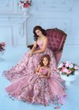 Mom and daughter in luxurious, pink dresses with sakura flowers on a skirt. Family clothes, identical dresses. The. Mom and daughter in luxurious, pink dresses Royalty Free Stock Image