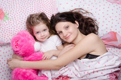 Mom and daughter lying in bed Stock Photo