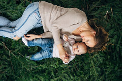 Mom and daughter are lying on Christmas trees. Mom and daughter are lying on spruce branches Royalty Free Stock Image