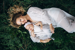 Mom and daughter are lying on Christmas trees. Mom and daughter are lying on spruce branches Royalty Free Stock Images