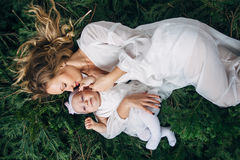 Mom and daughter are lying on Christmas trees. Mom and daughter are lying on spruce branches Stock Image
