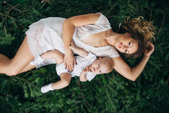 Mom and daughter are lying on Christmas trees. Mom and daughter are lying on spruce branches Royalty Free Stock Photography