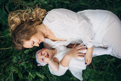 Mom and daughter are lying on Christmas trees Stock Images