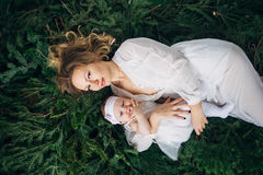 Mom and daughter are lying on Christmas trees Stock Photo