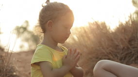 Mom and daughter meditate at sunrise stock video footage
