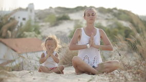 Mom and daughter meditate stock video footage
