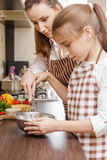 Mom and daughter mixing eggs in bowl with whisk Royalty Free Stock Photo