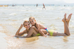 Mom and daughter on mother back lying on the beach. Mother and her sitting on the back of a four-year girl lying in the water on the sandy beach and happily look Stock Image