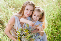 Mom and daughter in nature with a bouquet of wild flowers Royalty Free Stock Photography